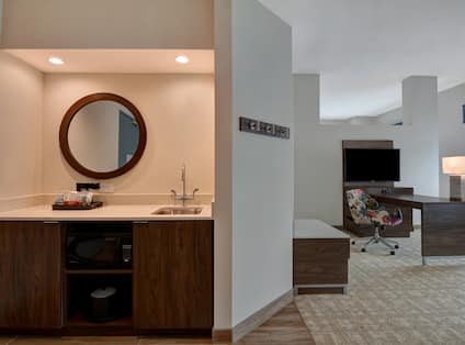 guest room with wet bar work desk and television