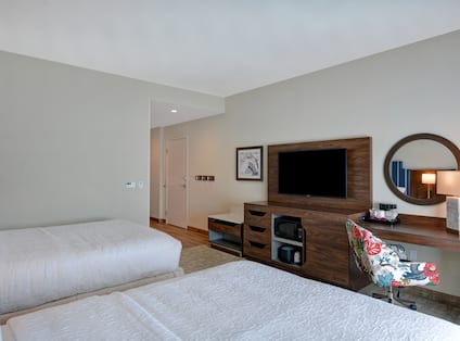 guest room with two beds work desk and television
