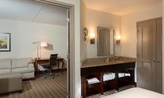 Suite Bedroom With Vanity Mirror, Sink, Fresh Towels and Open Doorway to View of Sofa and Work Desk in Living Area, and Bed