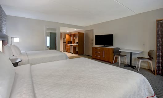 guest room with beds television and kitchen