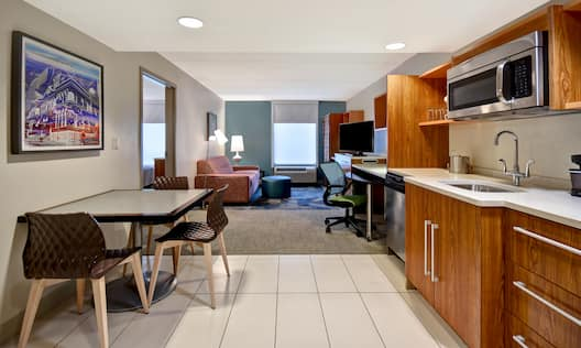 guest room with kitchen lounge area television work desk and window