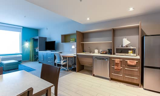 Overview of suite with dining area in foreground, kitchen with sink, fridge, mini oven, and work desk, television and lounge area beside