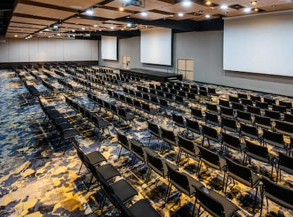 Large Meeting Room Setup Theater Style with Three Projection Screens