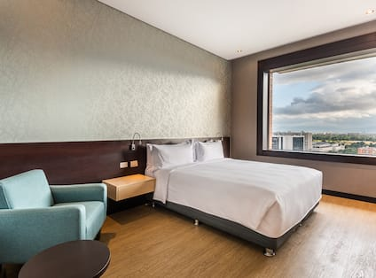 Guest Room with Large Bed Armchair and City View