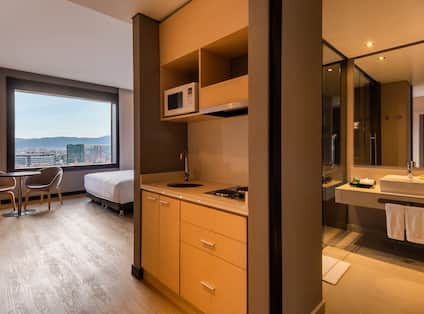 Overview of Hotel Room Kitchen Area Bedroom with City View and Bathroom Vanity