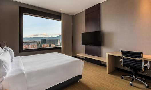 Bed in Guest Room with Desk HDTV and City View