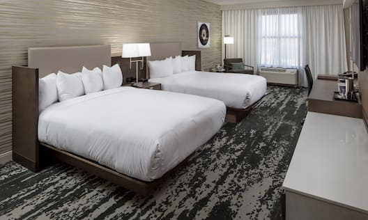 Two Queen Beds Guest Bedroom with Armchair and Work Desk