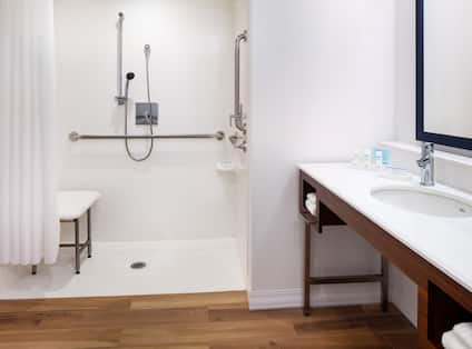 accessible rollin shower with seat and view of vanity area