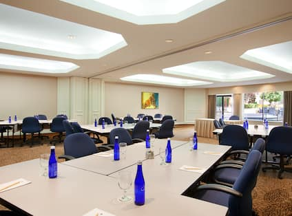 Bottled Water and Seating for 8 Around Tables Set up in Classroom Pods, Speaker's Table, and Wall Art in Bedford Meeting Room
