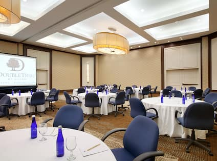 Blue Chairs, Round Dining Tables With Water Bottles and Glasses on White Linens, and Presentation Screen in Quincy Suite Meeting Room