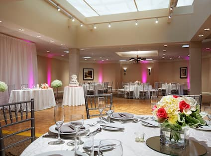 Round Tables With Place Settings and Flowers on White Linens, Dance Floor, and Table With Wedding Cake in Concord Meeting Room