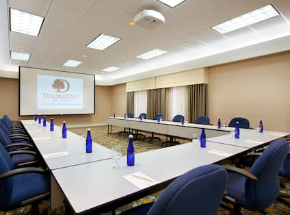 Middlesex Meeting Room With Water Bottles and Glasses on U-Table, Blue Chairs and Presentation Screen