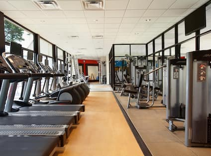 Fitness Center With Cardio Machines Facing Large Windows With Outside Views, TV, Weight Machines and Weight Benches