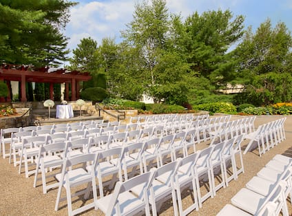 Angled View of Upper Terrace Set Up for Wedding Ceremony With White Chairs Arranged in Theater Style Facing Pavilion