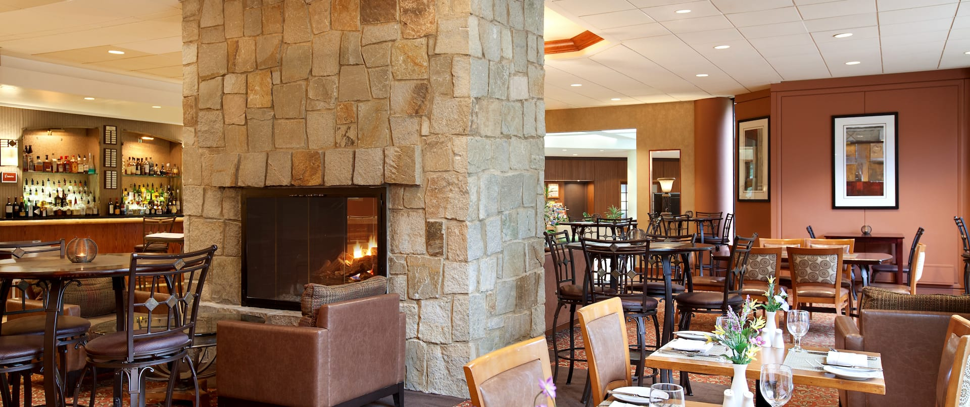 Tables, Chairs, Fireplace, and Fully Stocked Bar in SORA Restaurant