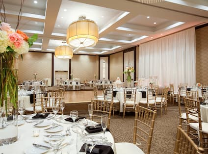 Tables With Flowers and Place Settings on White Linens Decorated for Wedding Reception by Dance Floor in Grand Ballroom