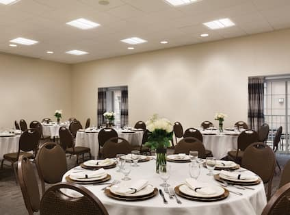 Round Tables With White Roses and Place Settings on White Linens in White Rose Meeting Room