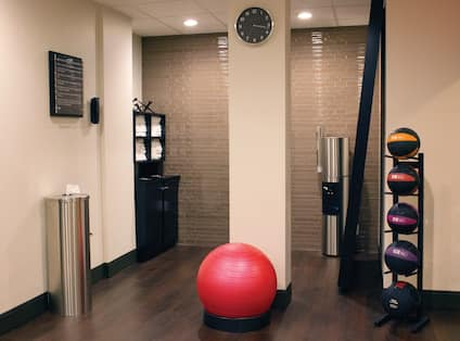 Fitness Center With Towel Station, Wall Clock, Red Exercise Ball, Water Cooler, Large Mirror, and Weight Balls