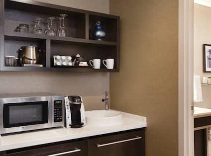 Guest Room Wet Bar With Drinkware on Shelves, Microwave, Keurig, Sink and Mini Fridge