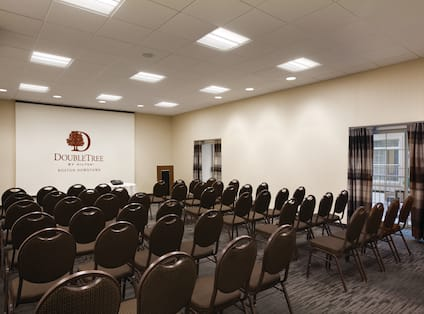 White Rose Meeting Room Arranged Theater Style With Rows of Chairs Facing Projector Screen and Podium