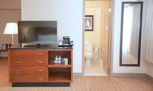 Detailed View of Media Center With TV and Coffee Maker, Open Doorway to Bathroom, Full Length Mirror by Window With Sheer Drapes in Deluxe and Executive Rooms