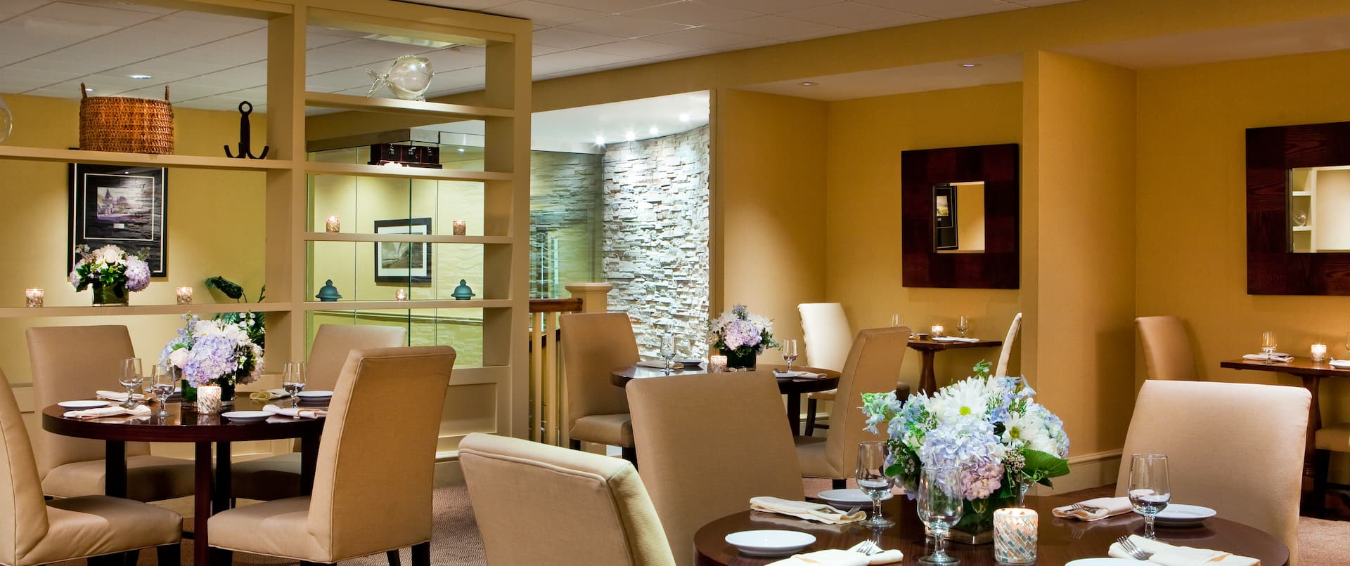 Shelves, Wall Mirrors, Dining Tables With Place Settings, Flowers, and Chairs in TradeWinds Restaurant Lounge Library