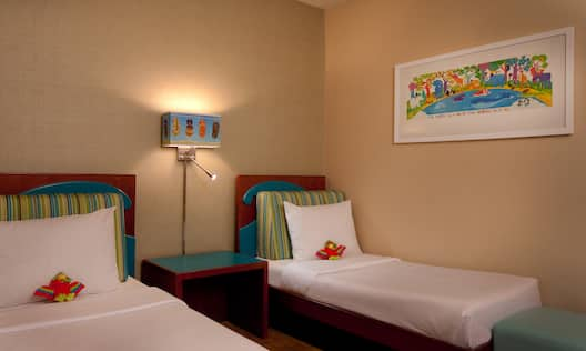 Brightly Decorated Room With Small Beds and Illuminated Lamp on Bedside Table in Child Room of Family Suite