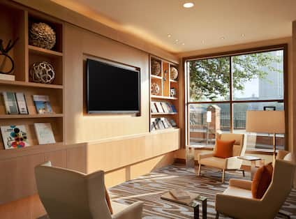 Decorated Shelves, TV, Armchairs, Tables, and Window With Outside View in Lobby Seating Area