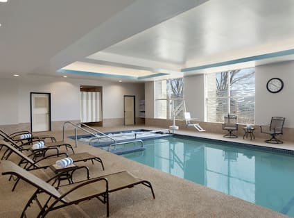 Tables, Chairs, and Relaxation Loungers by Heated Indoor Pool
