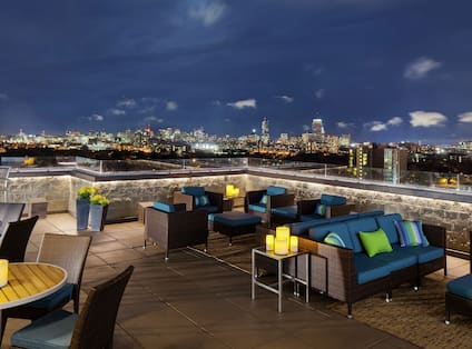 Candlelit Tables and Lounge Seating on Roof Deck and Illuminated Boston Skyline at Night