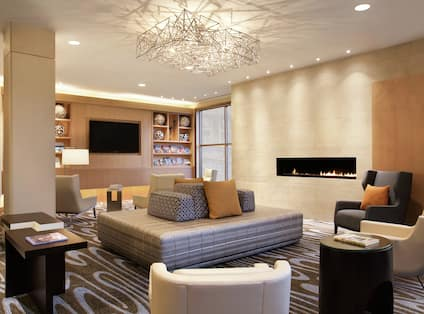 Soft Seating Around Fireplace in Lobby Lounge Area With TV and Window