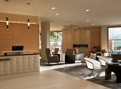 Soft Seating in Lobby Lounge Area With View of Concierge Desk, Fireplace, and Business Centr