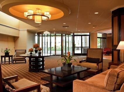 Tables, Lounge Seating, Illuminated Lights, and Glass Door Entrance in Main Lobby