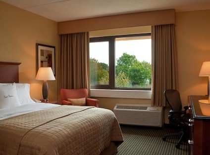 King Bed, Illuminated Lamp on Bedside Table, Wall Art, Reading Chair in Corner by Window With Open Drapes, Illuminated Lamp on Work Desk, and a TV in Accessible Room