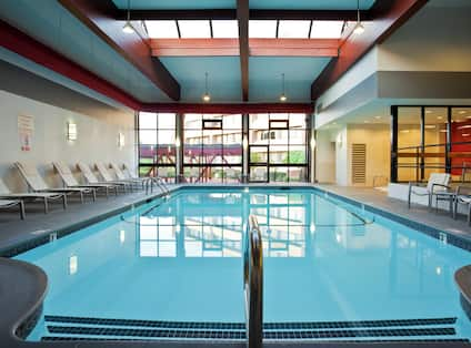 Loungers, Tables, Chairs, and Windows Around Heated Indoor Pool With Skylights