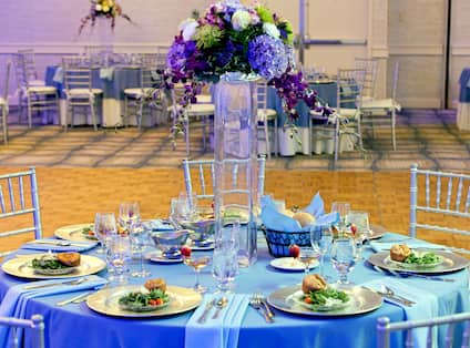 Grand  Ballroom Set Up for Wedding Reception With Dramatic Purple Lighting, Plates of Food, and Purple Flowers on Round Tables With Blue Linens and Chairs by Dance Floor