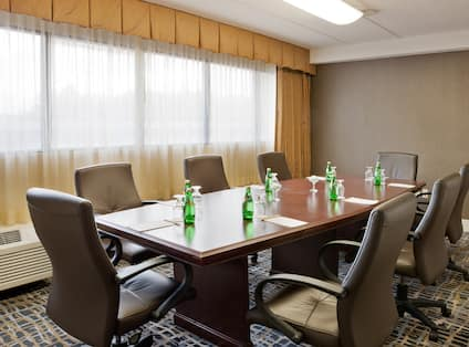 LArge Window With Sheer Drapes, and Seating For 8 Around Large Wood Table in Executive Boardroom