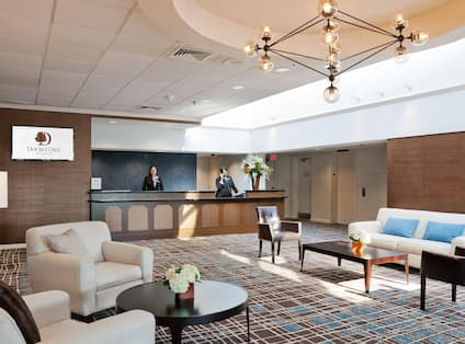 Two Female Staff Members Behind Front Desk and Spacious Lobby With TV, Soft Seating, and Illuminated Lamps in Lounge Area