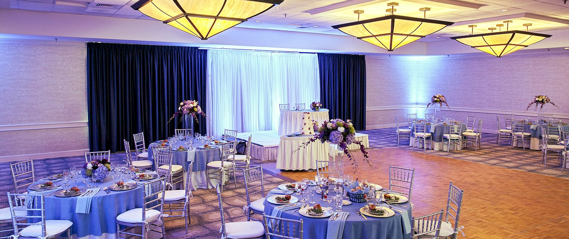 Grand Ballroom Set Up for Wedding Reception With Dramatic Purple Lighting, Head Table on a Stage, Cake Table By Dance Floor, Plates of Food, and Purple Flowers on Round Tables With Blue Linens and Chairs