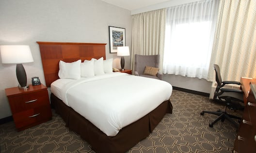 King Bed, Illuminated Lamps on Bedside Tables, Wall Art, Armchair, Window With Sheer Drapes, and Work Desk in Accessible Room