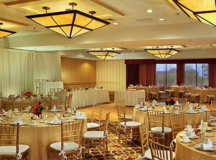 Ballroom Set Up for Wedding Reception With Head and Cake Tables By Dance Floor, Place Settings, and Flowers on Round Tables With Gold Linens and Chairs