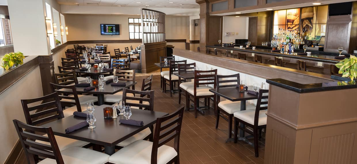 TV, Tables, Chairs, and Bar Seating in Dining Area of Regatta Grille