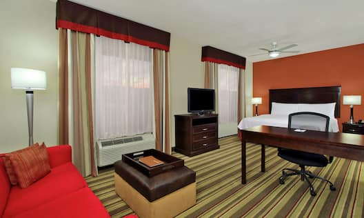 King-Size Bed, Work Desk with Chair, TV, and Couch in Studio Suite