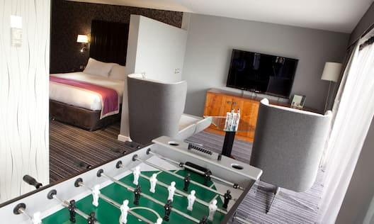 Panoramic Suite With Illuminated Lamp by Bed Behind Partition, Living Area With TV, Two Grey Armchairs, and Sheer Drapes by Balcony With a View, and Foosball Table
