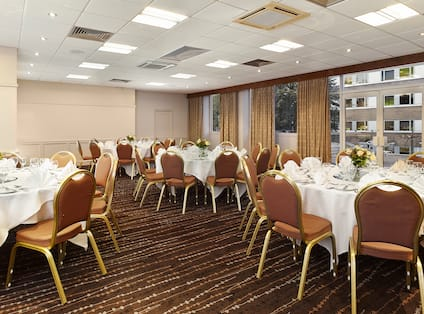 Park Suite Meeting Space With Chairs, Round Tables With Place Settings and Flowers on White Linens, Windows With Open Open Drapes