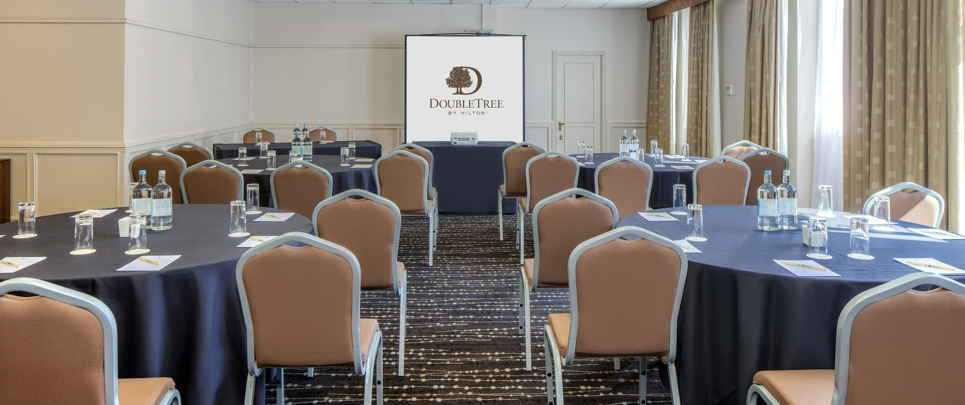 Table With Projector in Front of Presentation Screen, and Water Bottles and Glasses on Round Dining Tables With Black Linens in Park Suite