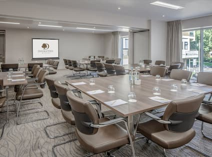 Presentation Screen, Water Bottles and Glasses on Wood Tables, and Large Windows With Open Drapes in Clifton Harbourside Suite