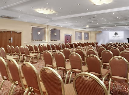 Ballroom Arranged Theater Style With Rows of Chairs Facing Projector Screen and Podium
