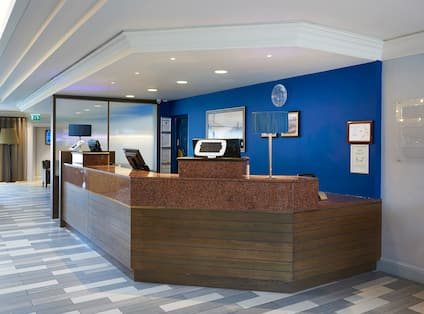 Diagonal View of Front Desk In Front of Blue Wall With Three Reception Stations and Lobby With Seating Area in Background