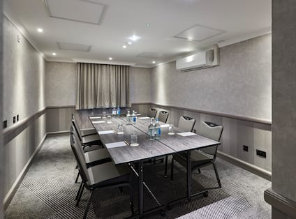Window With Closed Drapes and Seating for 8 at Large Table With Water Bottles and Glasses in Boardroom